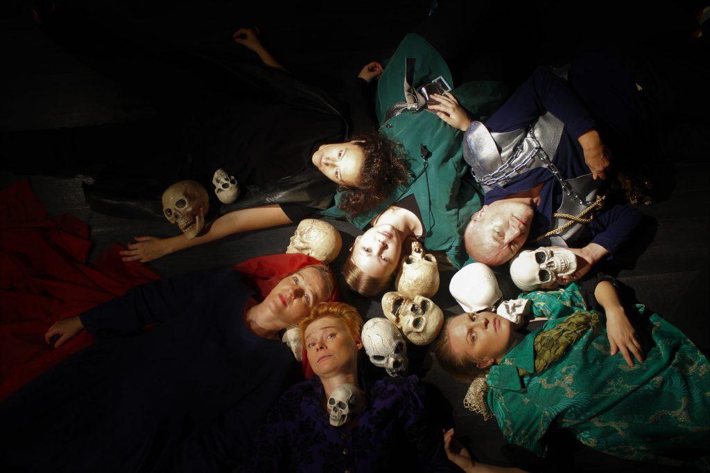 HC Macbeth -hahmot makaavat lattialla pääkallojen kanssa.