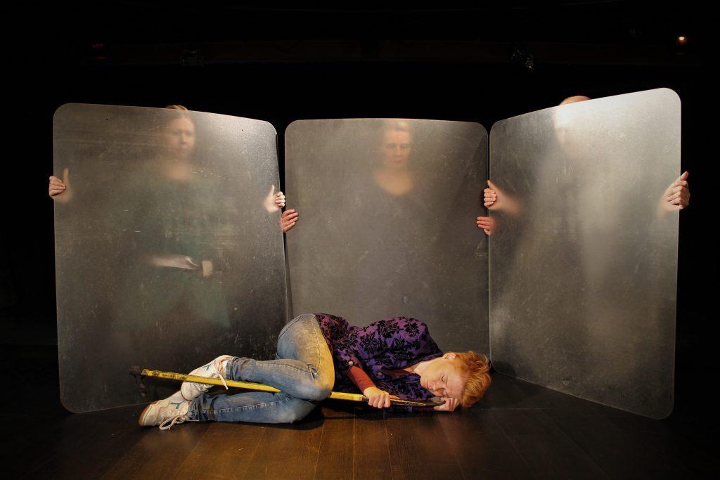 Macbeth makaa lattialla ja muut hahmot katselevat pleksien läpi taustalla.