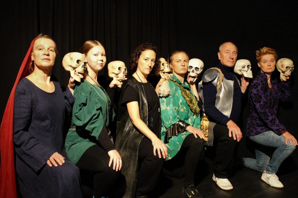 HC Macbeth -hahmot kyykistyneinä rivissä pääkallojen kanssa.