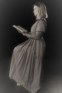 Musta-valkoinen, vanhaksi käsitelty kuva, jossa tyttö lukee kirjaa.