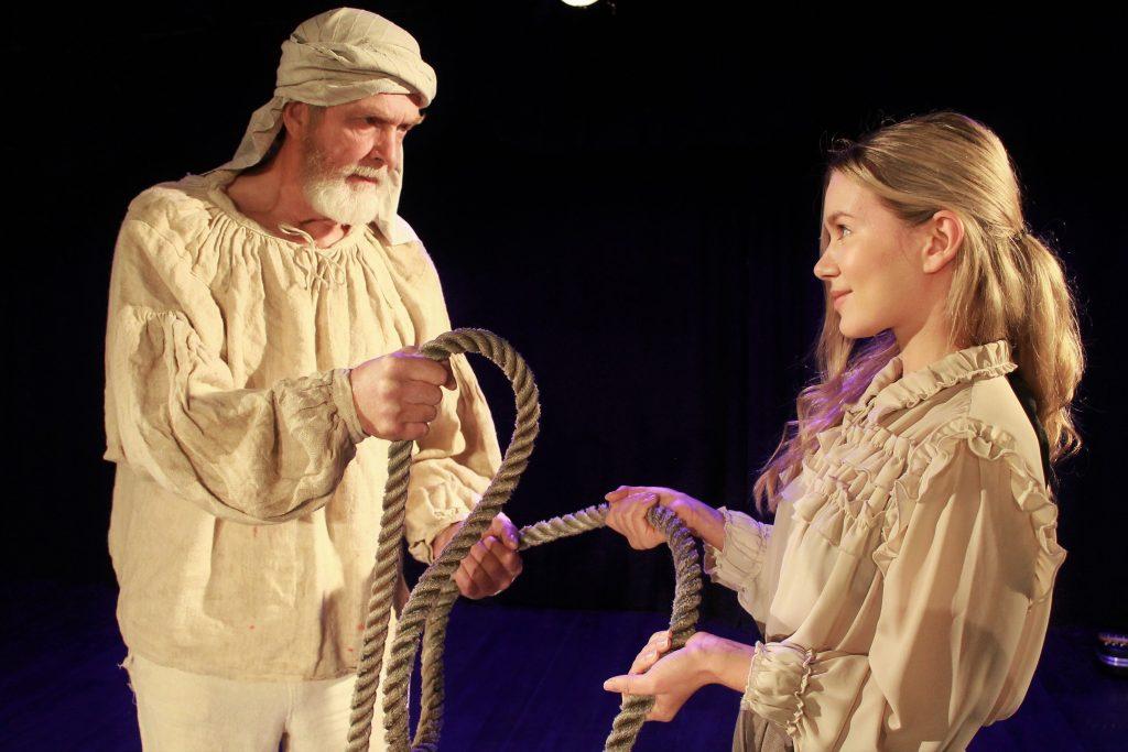 Kaksi roolihahmoa, vanhempi mies ja nuori nainen katsovat toisiaan ja pitävät molemmat kiinni köydestä.