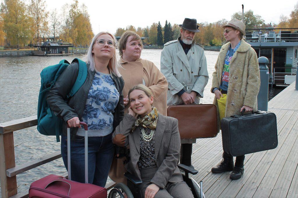 Viisi näytelmähahmoa ovat ulkona laiturilla ja he ovat odottavaisen näköisiä. Neljä hahmoista seisoo ja yksi istuu pyörätuolissa.
