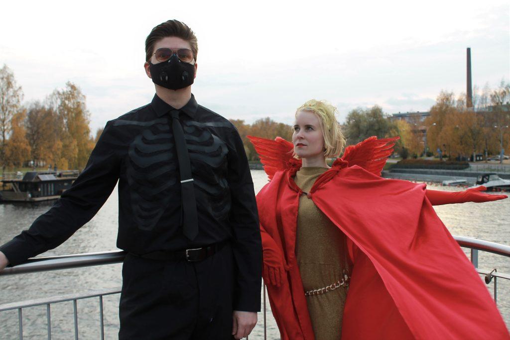 Mustiin pukeutunut hahmo, jolla on naamio päässään seisoo veden äärellä. Hänen vieressään on punaiseen viittaan pukeutunut enkelisiipinen hahmo.